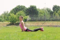 Estómago atlético de la hierba del estiramiento de la cobra de la muchacha que hace frente al piso Foto de archivo
