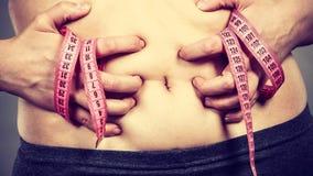 Estómago conmovedor de la mujer que detiene a la cinta métrica Fotografía de archivo libre de regalías