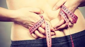 Estómago conmovedor de la mujer que detiene a la cinta métrica Imagen de archivo libre de regalías