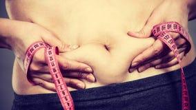 Estómago conmovedor de la mujer que detiene a la cinta métrica Imagen de archivo