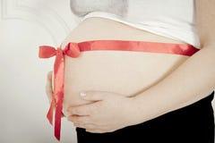 Estómago de la muchacha embarazada con un arqueamiento rojo Fotos de archivo libres de regalías