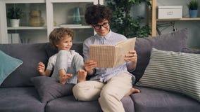 Estória boa de leitura da mulher alegre ao rapaz pequeno que ri tendo o divertimento em casa