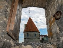 ESTÔNIA, TALLINN - 26 DE JUNHO DE 2015: Vista da torre da fortaleza através da janela antiga foto de stock royalty free