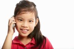 Estúdio disparado da menina chinesa com telefone móvel Fotografia de Stock