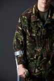 Estúdio disparado de soldado ferido Using Crutch Imagens de Stock Royalty Free