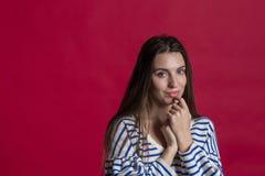 Estúdio disparado de uma mulher bonita bonita contra uma parede vermelha vazia do estúdio fotos de stock royalty free