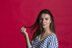 Estúdio disparado de uma mulher bonita bonita isolada contra uma parede vermelha vazia do estúdio fotografia de stock