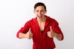 Estúdio disparado do homem considerável novo feliz que sorri ao dar thu fotos de stock royalty free
