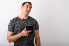 Estúdio disparado do homem muscular novo que pensa ao apontar ao imagens de stock