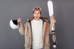 Estúdio do homem novo isolado no estilo cinzento do inverno que mantém o capacete e os esquis entusiasmado imagens de stock
