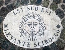Est Sud Est. East South East - a head symbolizing the direction of the wind. An ancient image on a marble slab in St. Peter`s Squa. Re in the Vatican. Europe Royalty Free Stock Images