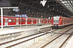 Estação de caminhos-de-ferro classicistic do ferro com trens vermelhos Fotografia de Stock