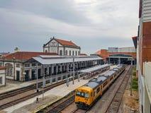 Estação de caminhos de ferro com diversos linhas e trem amarelo na plataforma, Portugal foto de stock