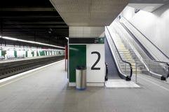 Estação de comboio com plataformas e as escadas rolantes de sinalização fotografia de stock royalty free
