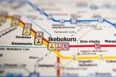 Estação de metro do Tóquio de Ikebukuro em um mapa impresso do metro de Paris sob uma lente da lente de aumento foto de stock