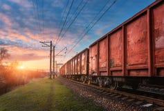 Estação de trem com vagões e trem da carga no por do sol foto de stock