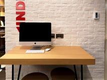 Estação do espaço de trabalho do escritório com o computador de iMac da maçã em uma tabela de madeira imagem de stock