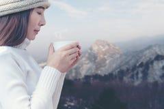 Estação do inverno A mão do ` s da mulher que guarda uma xícara de café branca em árvores de Natal da neve, relaxa e feliz no dia imagens de stock royalty free