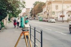 Estação total eletrônica do dispositivo do topógrafo na rua Medida do relevo fotografia de stock