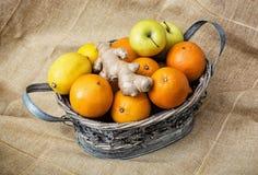 Estañe la cesta de mimbre con las manzanas, las naranjas, los limones y el jengibre Foto de archivo