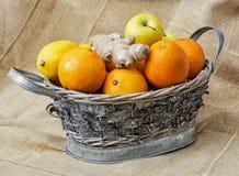 Estañe la cesta de mimbre con las manzanas, las naranjas, los limones y el jengibre, healt Foto de archivo libre de regalías