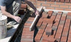 Pedreiro do tijolo que coloca um passeio Imagens de Stock Royalty Free