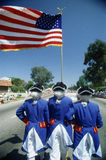 Esta é uma parada do Dia da Independência com os homens vestidos como os soldados revolucionários da guerra que prendem a bandeir Imagens de Stock Royalty Free