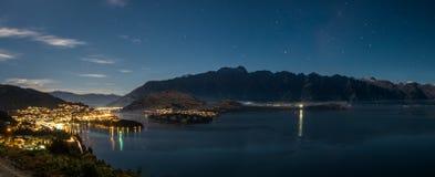 Esta foto panorâmico foi tomada sobre um monte em Queenstown, Nova Zelândia Era noite e a cidade ilumina-se acima belamente fotos de stock