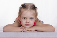 Esta menina tem sua cabeça em suas mãos e olha no quadro Imagens de Stock