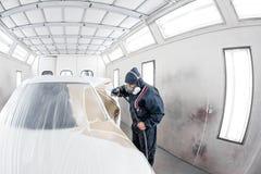 Esta??o do servi?o do carro trabalhador que pinta um carro branco na garagem especial, no traje vestindo e na engrenagem protetor fotos de stock royalty free