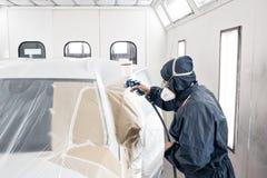 Esta??o do servi?o do carro trabalhador que pinta um carro branco na garagem especial, no traje vestindo e na engrenagem protetor fotos de stock