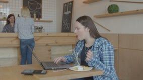 Establecimiento de una red confiado del freelancer en el ordenador portátil en café almacen de video