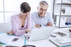 Establecimiento de una red de los oficinistas con un ordenador portátil Imagen de archivo libre de regalías