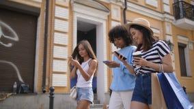 Establecimiento de una red diverso de las muchachas con los teléfonos móviles en la calle metrajes