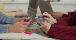 Establecimiento de una red humano de las manos con los dispositivos digitales en el escritorio almacen de metraje de vídeo
