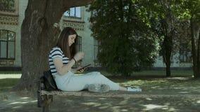 Establecimiento de una red precioso de la muchacha con PC de la tableta en el banco almacen de video
