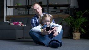 Establecimiento de una red de reclinación de la muchacha del papá y del preadolescente en el teléfono almacen de metraje de vídeo