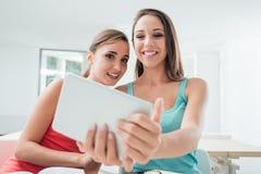 Establecimiento de una red social de las muchachas con una tableta Imagen de archivo