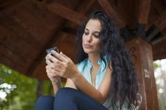 Establecimiento de una red social - uso sonriente joven pH móvil de la mujer de la raza mixta Fotos de archivo libres de regalías