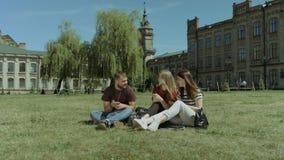 Establecimiento de una red sonriente de los estudiantes con los teléfonos elegantes en césped metrajes
