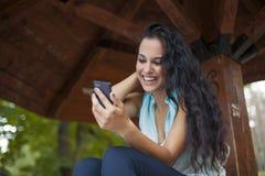 Establecimiento de una red - teléfono móvil sonriente joven del uso de la mujer de la raza mixta a Foto de archivo