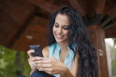 Establecimiento de una red - teléfono móvil sonriente joven del uso de la mujer de la raza mixta a Foto de archivo libre de regalías