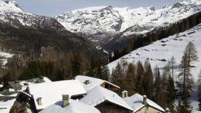Establisher трутня зимы воздушное над снежной долиной древесин городка и леса под замороженными горами Снег в природе горы сток-видео