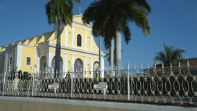 Establishing shoot of a church in Trinidad on Cuba. An establishing shoot of a yellow church in Trinidad on Cuba. Some Palm trees with moving leaves in the stock video