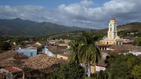 Establishing shoot in the town of Trinidad on Cuba. An establishing shoot of the town of Trinidad on Cuba. In the foreground a moving palm tree in the wind. A stock video