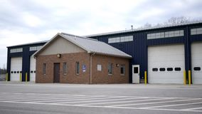 Establishing shot of Blue warehouse building on overcast day stock footage