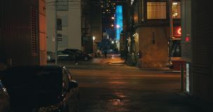 Establishing shot of a dark alleyway at night. Atmospheric 4K footage. Shot on a cinema camera in RAW. No discernible faces or logos stock footage