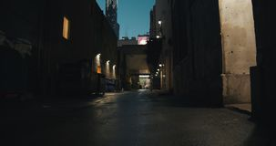 Establishing shot of a dark alleyway at night. Atmospheric 4K footage. Shot on a cinema camera in RAW. No discernible faces or logos stock video footage