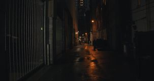 Establishing shot of a dark alleyway at night. Atmospheric 4K footage. Shot on a cinema camera in RAW. No discernible faces or logos stock video