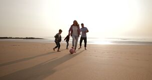 Playing Football on the Beach. Establishing shot of a family playing football while on holiday at the seaside stock footage